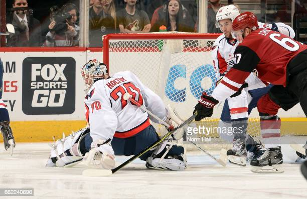 Goalie Braden Holtby of the Washington Capitals reaches back to cover the puck as Lawson Crouse of the Arizona Coyotes tries to get a shot off the...