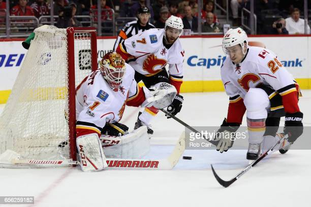 Goalie Brian Elliott of the Calgary Flames blocks a shot as TJ Brodie and Michael Stone look on against the Washington Capitals in the second period...