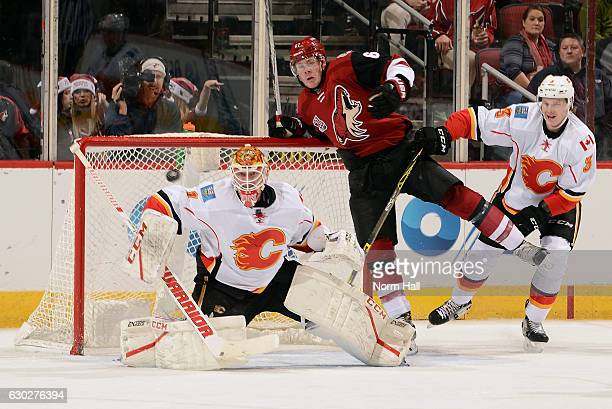 Goalie Brian Elliott of the Calgary Flames makes a save on a shot as Lawson Crouse of the Arizona Coyotes and Jyrki Jokipakka of the Flames battle in...
