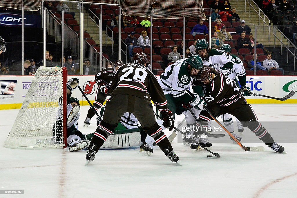 Goalie Cab Morris #1 of the Dartmouth Big Green is pressured by center Mark Naclerio #27 and Nick Lappin #28 of the Brown Bears at Prudential Center on October 26, 2013 in Newark, New Jersey. The Brown Bears defeated the Dartmouth Big Green, 5-3.