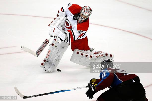 Goalie Cam Ward of the Carolina Hurricanes clears the puck against Gabriel Landeskog of the Colorado Avalanche at Pepsi Center on October 21 2015 in...