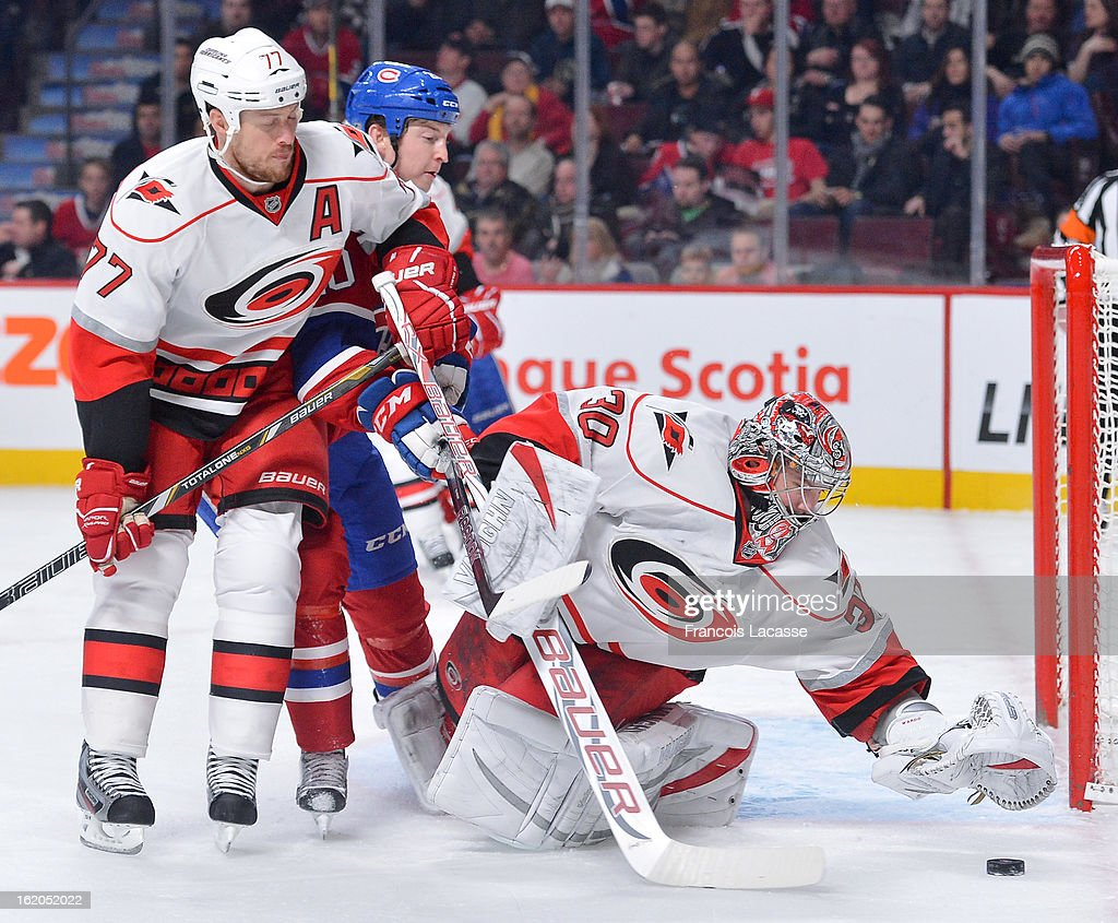 Goalie Cam Ward #30 of the Carolina Hurricanes comes out of his net to cover a loose puck as teammate Joe Corvo #77 ties up Colby Armstrong #20 of the Montreal Canadiens during the NHL game on February 18, 2013 at the Bell Centre in Montreal, Quebec, Canada.