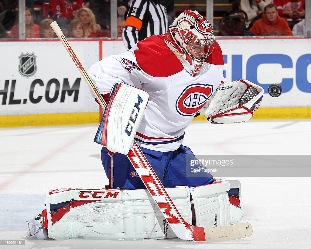 Goalie <a gi-track='captionPersonalityLinkClicked' href=/galleries/search?phrase=Carey+Price&family=editorial&specificpeople=2222083 ng-click='$event.stopPropagation()'>Carey Price</a> #31 of the Montreal Canadiens makes a glove save during an NHL game against the Detroit Red Wings on March 27, 2014 at Joe Louis Arena in Detroit, Michigan.