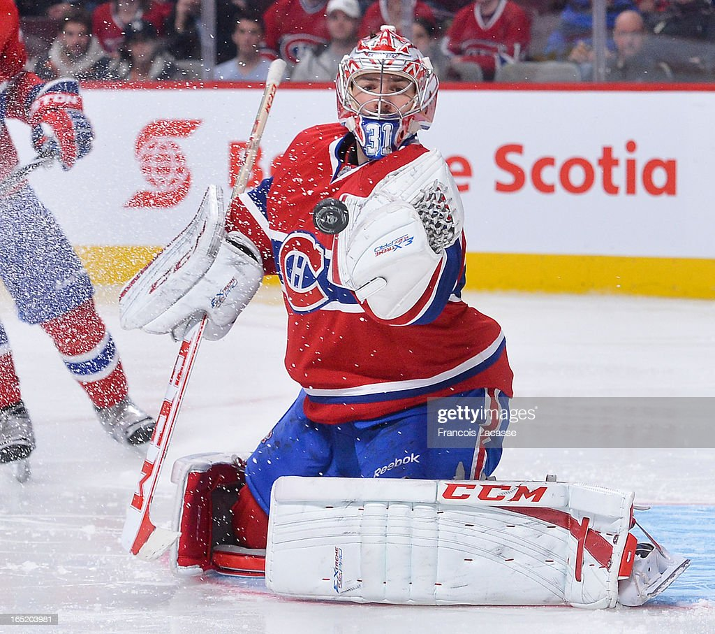 Goalie <a gi-track='captionPersonalityLinkClicked' href=/galleries/search?phrase=Carey+Price&family=editorial&specificpeople=2222083 ng-click='$event.stopPropagation()'>Carey Price</a> #31 of the Montreal Canadiens makes a glove save against the Carolina Hurricanes during the NHL game on April 1, 2013 at the Bell Centre in Montreal, Quebec, Canada.