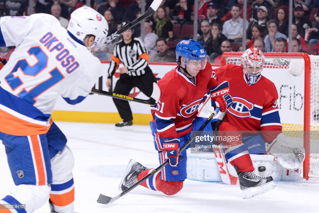 Goalie <a gi-track='captionPersonalityLinkClicked' href=/galleries/search?phrase=Carey+Price&family=editorial&specificpeople=2222083 ng-click='$event.stopPropagation()'>Carey Price</a> #31 of the Montreal Canadiens stops the puck on a shot by <a gi-track='captionPersonalityLinkClicked' href=/galleries/search?phrase=Kyle+Okposo&family=editorial&specificpeople=540469 ng-click='$event.stopPropagation()'>Kyle Okposo</a> #21 of the New York Islanders during the NHL game at the Bell Centre on February 21, 2013 in Montreal, Quebec, Canada. The Islanders defeated the Canadiens 4-3 in overtime.