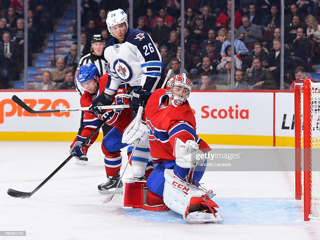 Goalie <a gi-track='captionPersonalityLinkClicked' href=/galleries/search?phrase=Carey+Price&family=editorial&specificpeople=2222083 ng-click='$event.stopPropagation()'>Carey Price</a> #31 of the Montreal Canadiens watches the puck pass by the net as teammate <a gi-track='captionPersonalityLinkClicked' href=/galleries/search?phrase=Raphael+Diaz&family=editorial&specificpeople=5333791 ng-click='$event.stopPropagation()'>Raphael Diaz</a> #61 battles for position against Blake Weeler #26 of the Winnipeg Jets during the NHL game on January 29, 2013 at the Bell Centre in Montreal, Quebec, Canada.