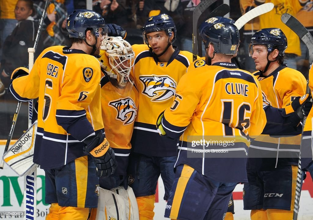 Goalie Carter Hutton #30 of the Nashville Predators is congratulated by teammates Shea Weber #6, Seth Jones #3, Rich Clune #16, and Gabriel Bourque #57 after defeating the Tampa Bay Lightning at Bridgestone Arena on February 27, 2014 in Nashville, Tennessee.