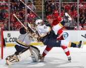 Goalie Chris Mason of the Nashville Predators tries to locate the puck as teamate Roman Josi gets taken out by Daniel Cleary of the Detroit Red Wings...