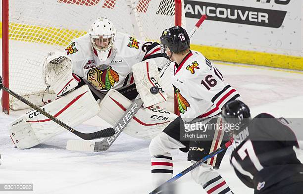 Goalie Cole Kehler of the Portland Winterhawks stops the shot of Tyler Benson of the Vancouver Giants as Henri Jokiharju of the Winterhawks looks on...