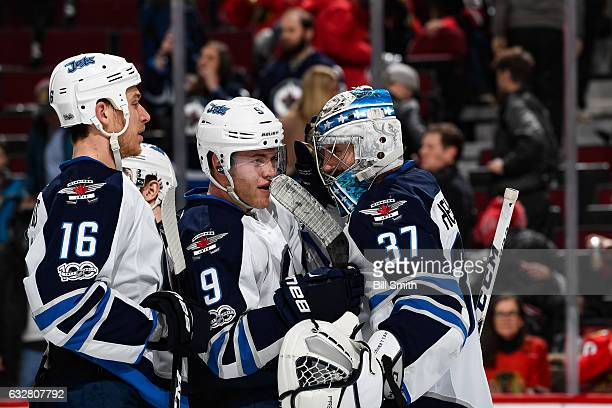 Goalie Connor Hellebuyck Andrew Copp and Shawn Matthias of the Winnipeg Jets celebrate after defeating the Chicago Blackhawks 53 at the United Center...