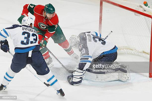 Goalie Connor Hellebuyck makes a save while his Winnipeg Jets teammate Dustin Byfuglien defends Chris Porter of the Minnesota Wild during the game on...