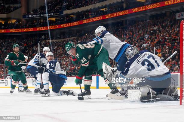 Goalie Connor Hellebuyck makes a save while his Winnipeg Jets teammates Josh Morrissey Brandon Tanev and Jacob Trouba defend against Jason Zucker and...