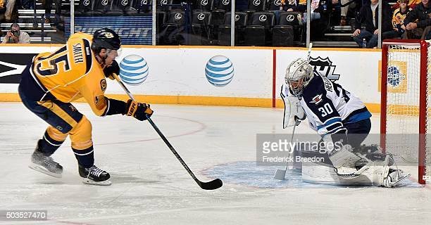 Goalie Connor Hellebuyck of the Winnipeg Jets makes a glove save on a break away shot by Craig Smith of the Nashville Predators during the first...