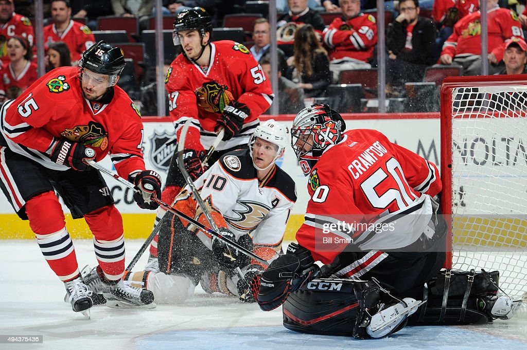 Goalie Corey Crawford and Artem Anisimov of the Chicago Blackhawks wait for the puck as Corey Perry of the Anaheim Ducks and Trevor van Riemsdyk...