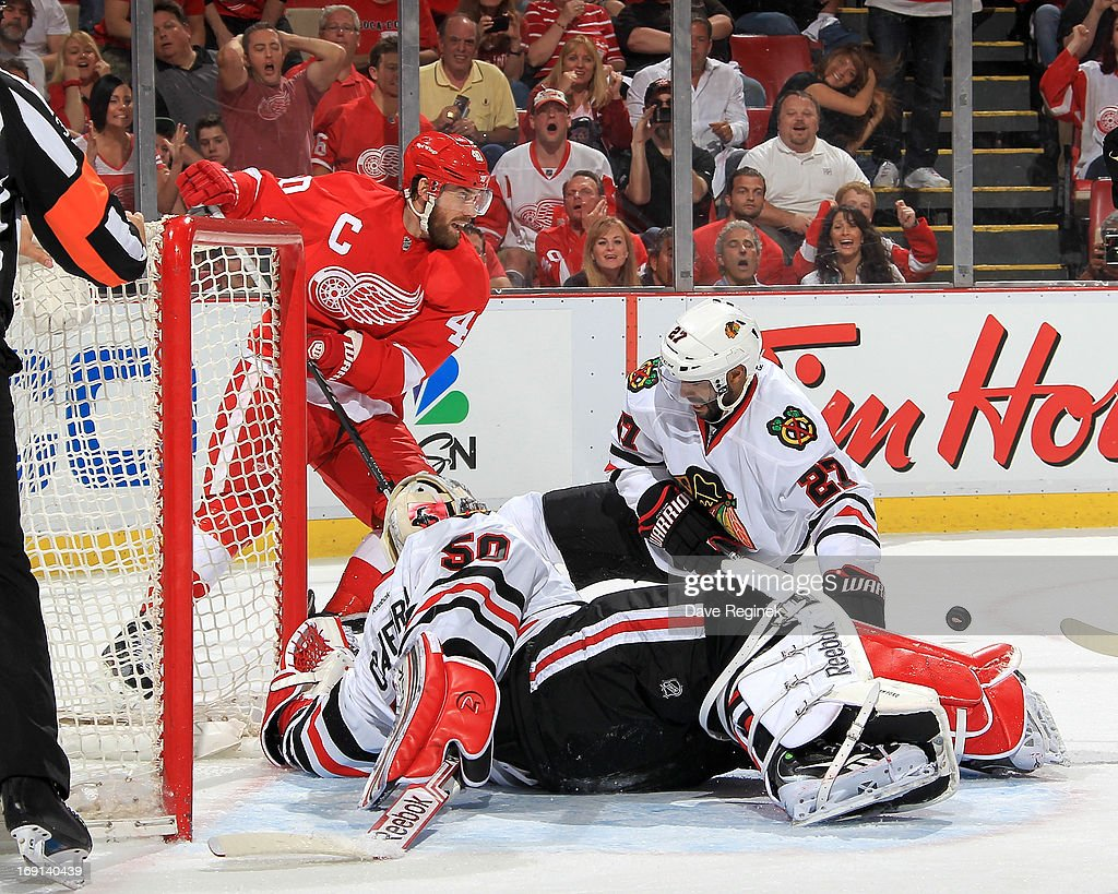 Goalie Corey Crawford #50 and Johnny Oduya #27 of the Chicago Blackhawks try to cover the net as Henrik Zetterberg #40 of the Detroit Red Wings goes after the rebounding puck during Game Three of the Western Conference Semifinals during the 2013 NHL Stanley Cup Playoffs at Joe Louis Arena on May 20, 2013 in Detroit, Michigan.
