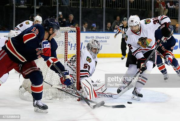 Goalie Corey Crawford of the Chicago Blackhawks and teammate Michal Rozsival combine to stop a shot by Brad Richards of the New York Rangers in the...