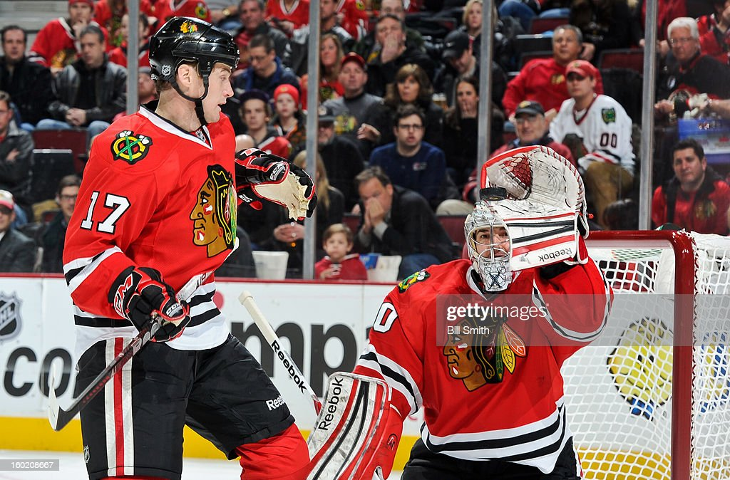 Goalie <a gi-track='captionPersonalityLinkClicked' href=/galleries/search?phrase=Corey+Crawford&family=editorial&specificpeople=818935 ng-click='$event.stopPropagation()'>Corey Crawford</a> #50 of the Chicago Blackhawks catches the puck next to teammate <a gi-track='captionPersonalityLinkClicked' href=/galleries/search?phrase=Sheldon+Brookbank&family=editorial&specificpeople=586095 ng-click='$event.stopPropagation()'>Sheldon Brookbank</a> #17 during the NHL game against the Detroit Red Wings on January 27, 2013 at the United Center in Chicago, Illinois.