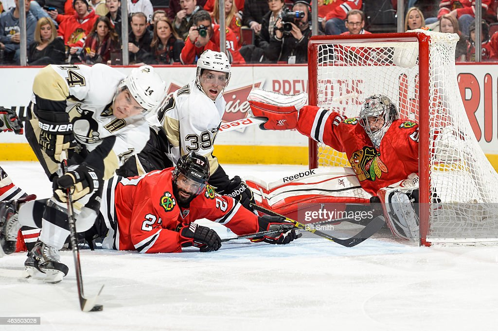 Goalie Corey Crawford of the Chicago Blackhawks falls into the net as David Perron of the Pittsburgh Penguins and Johnny Oduya watch Chris Kunitz...