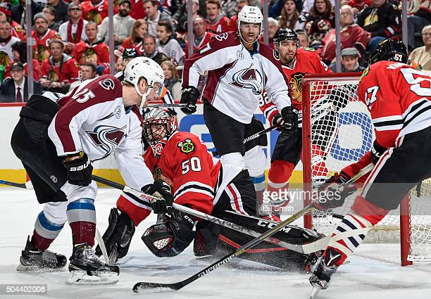 Goalie Corey Crawford of the Chicago Blackhawks is scored on as Mikhail Grigorenko of the Colorado Avalanche rushes in and Andreas Martinsen and...
