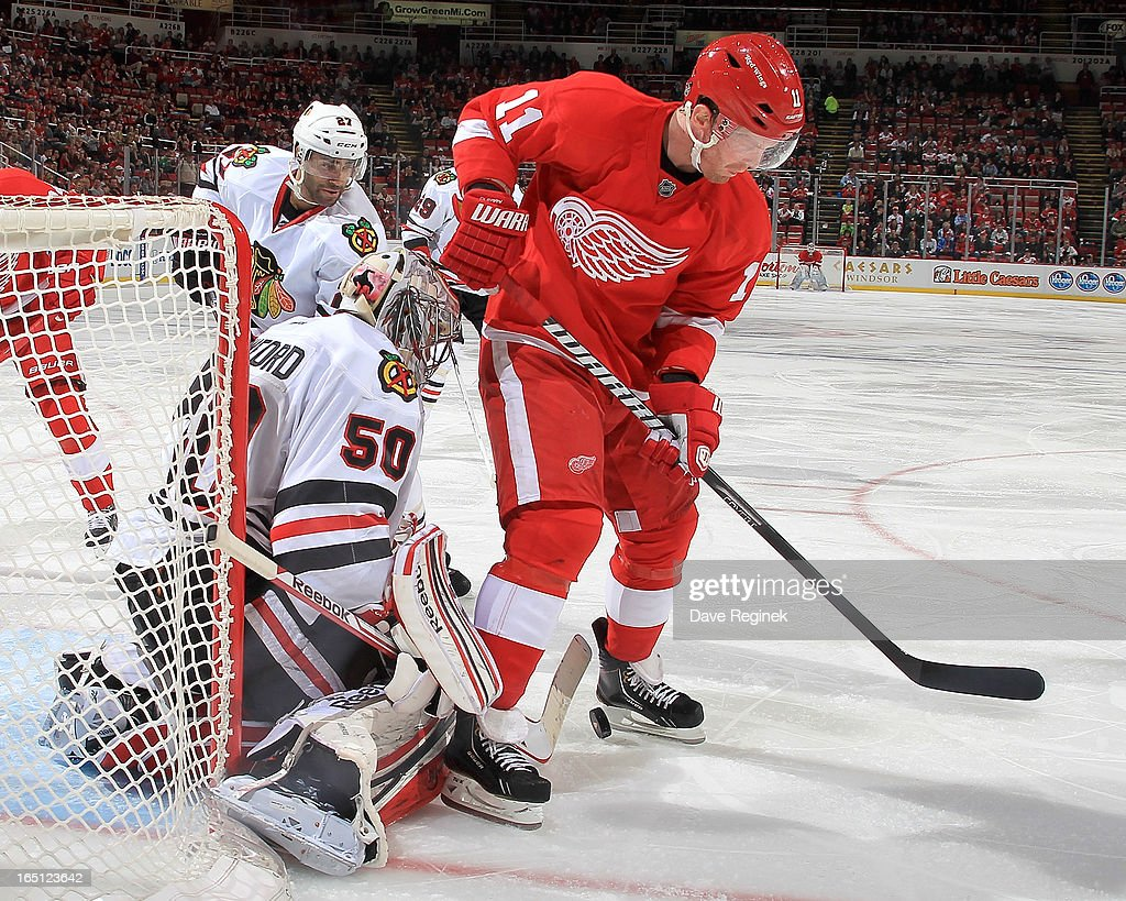 Goalie Corey Crawford #50 of the Chicago Blackhawks makes a save as Daniel Cleary #11 of the Detroit Red Wings tries to find the rebound between his feet during a NHL game at Joe Louis Arena on March 31, 2013 in Detroit, Michigan. Chicago defeated Detroit 7-1