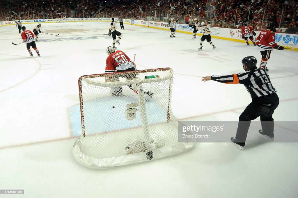 Goalie <a gi-track='captionPersonalityLinkClicked' href=/galleries/search?phrase=Corey+Crawford&family=editorial&specificpeople=818935 ng-click='$event.stopPropagation()'>Corey Crawford</a> #50 of the Chicago Blackhawks skates off of the ice as the Boston Bruins celebrate their 2-1 win in overtime of Game Two of the NHL 2013 Stanley Cup Final at United Center on June 15, 2013 in Chicago, Illinois.