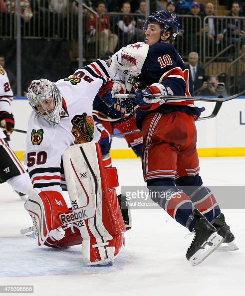Goalie Corey Crawford of the Chicago Blackhawks stops a shot and gets an elbow up to the face of JT Miller of the New York Rangers in the second...
