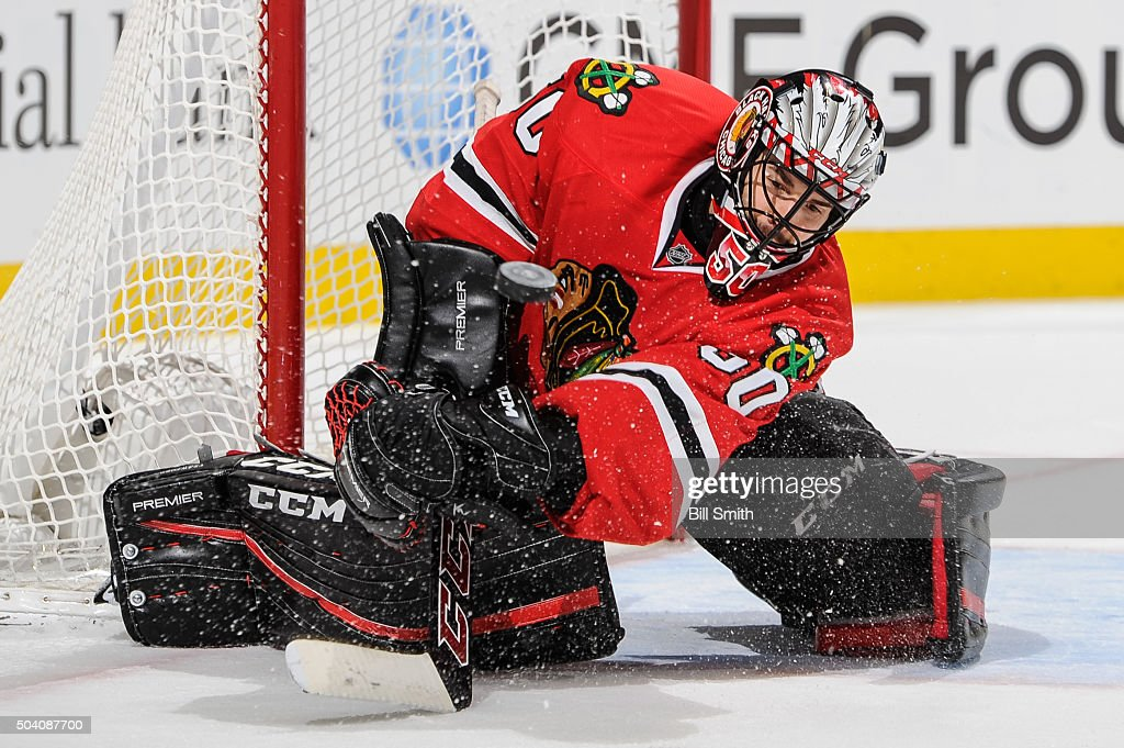 Goalie <a gi-track='captionPersonalityLinkClicked' href=/galleries/search?phrase=Corey+Crawford&family=editorial&specificpeople=818935 ng-click='$event.stopPropagation()'>Corey Crawford</a> #50 of the Chicago Blackhawks swipes at the puck in the third period of the NHL game against the Buffalo Sabres, where he made 28 saves, at the United Center on January 8, 2016 in Chicago, Illinois.