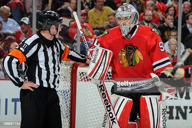 Goalie Corey Crawford of the Chicago Blackhawks talks with referee Kelly Sutherland in Game Five of the Western Conference Quarterfinals against the...