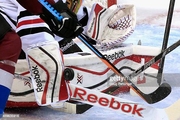 Goalie Corey Crawford of the Chicago Blackhawks turns away the puck and makes a save as he defends the goal against the Colorado Avalanche at Pepsi...