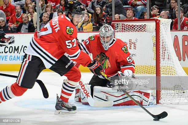 Goalie Corey Crawford of the Chicago Blackhawks watches Trevor van Riemsdyk handle the puck during the NHL game against the Nashville Predators on...