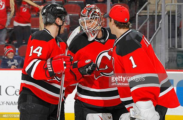 Goalie Cory Schneider of the New Jersey Devils celebrates with teammates Adam Henrique and Keith Kinkaid after defeating the Ottawa Senators at the...
