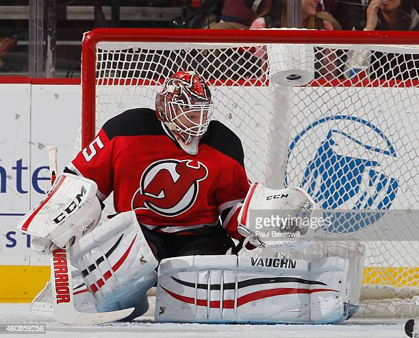 Goalie Cory Schneider of the New Jersey Devils makes a glove save in an NHL hockey game against the Carolina Hurricanes at Prudential Center on...