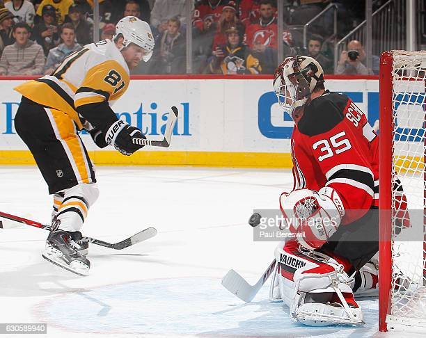 Goalie Cory Schneider of the New Jersey Devils stops a shot by Phil Kessel of the Pittsburgh Penguins in the first period of an NHL hockey game at...
