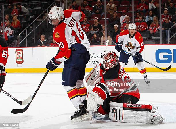 Goalie Cory Schneider of the New Jersey Devils stops a tipped shot by Reilly Smith of the Florida Panthers during the third period of an NHL hockey...