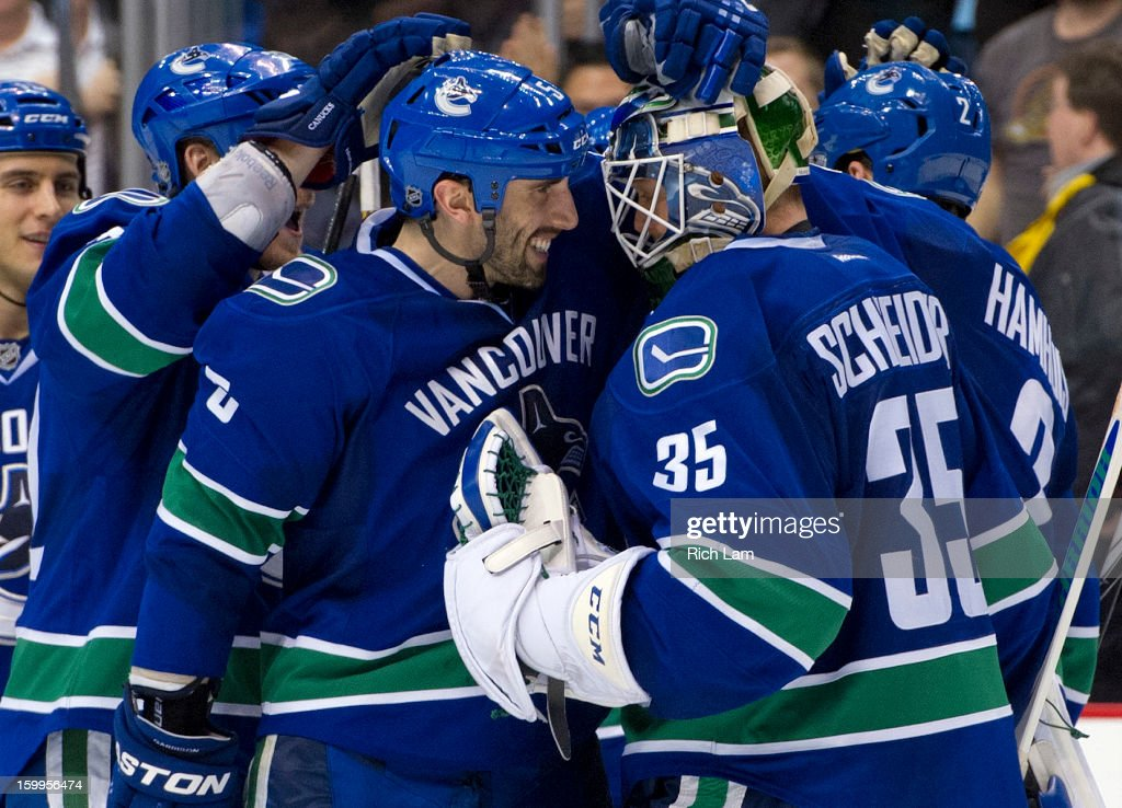Goalie <a gi-track='captionPersonalityLinkClicked' href=/galleries/search?phrase=Cory+Schneider&family=editorial&specificpeople=696908 ng-click='$event.stopPropagation()'>Cory Schneider</a> #35 of the Vancouver Canucks is congratulated by <a gi-track='captionPersonalityLinkClicked' href=/galleries/search?phrase=Jason+Garrison&family=editorial&specificpeople=2143635 ng-click='$event.stopPropagation()'>Jason Garrison</a> #5 after defeating the Calgary Flames 3-2 in a shootout during NHL action on January 23, 2013 at Rogers Arena in Vancouver, British Columbia, Canada.