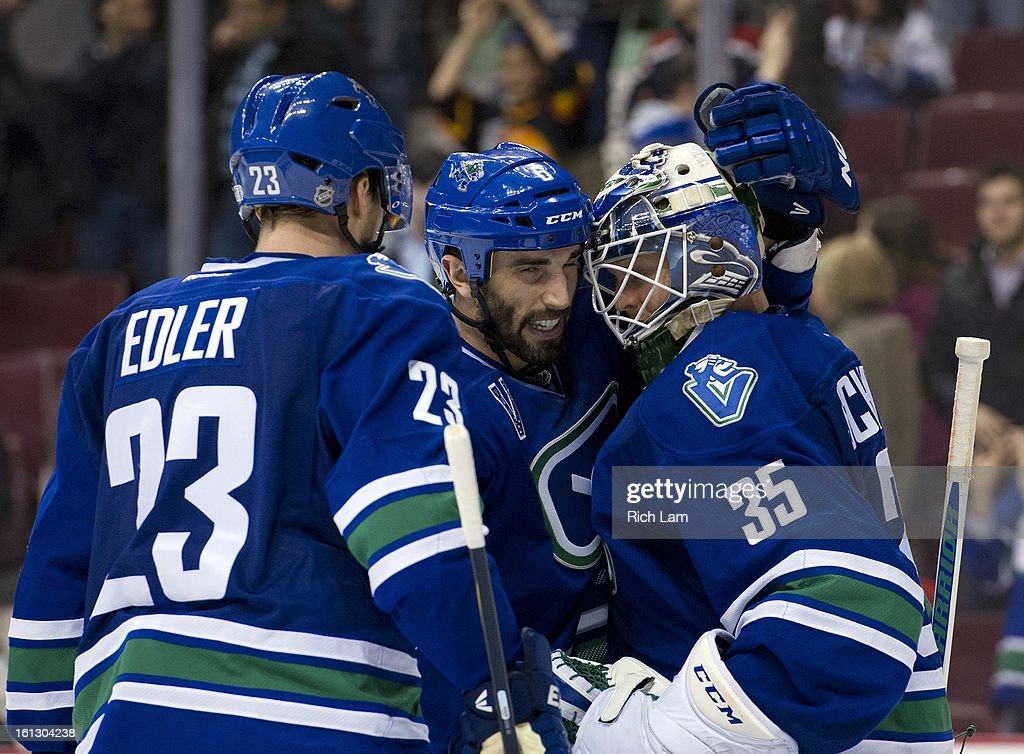 Goalie <a gi-track='captionPersonalityLinkClicked' href=/galleries/search?phrase=Cory+Schneider&family=editorial&specificpeople=696908 ng-click='$event.stopPropagation()'>Cory Schneider</a> #35 of the Vancouver Canucks is congratulated by <a gi-track='captionPersonalityLinkClicked' href=/galleries/search?phrase=Jason+Garrison&family=editorial&specificpeople=2143635 ng-click='$event.stopPropagation()'>Jason Garrison</a> #5 and <a gi-track='captionPersonalityLinkClicked' href=/galleries/search?phrase=Alexander+Edler&family=editorial&specificpeople=882987 ng-click='$event.stopPropagation()'>Alexander Edler</a> #23 after defeating the Calgary Flames 5-1 during the NHL action on February 09, 2013 at Rogers Arena in Vancouver, British Columbia, Canada.