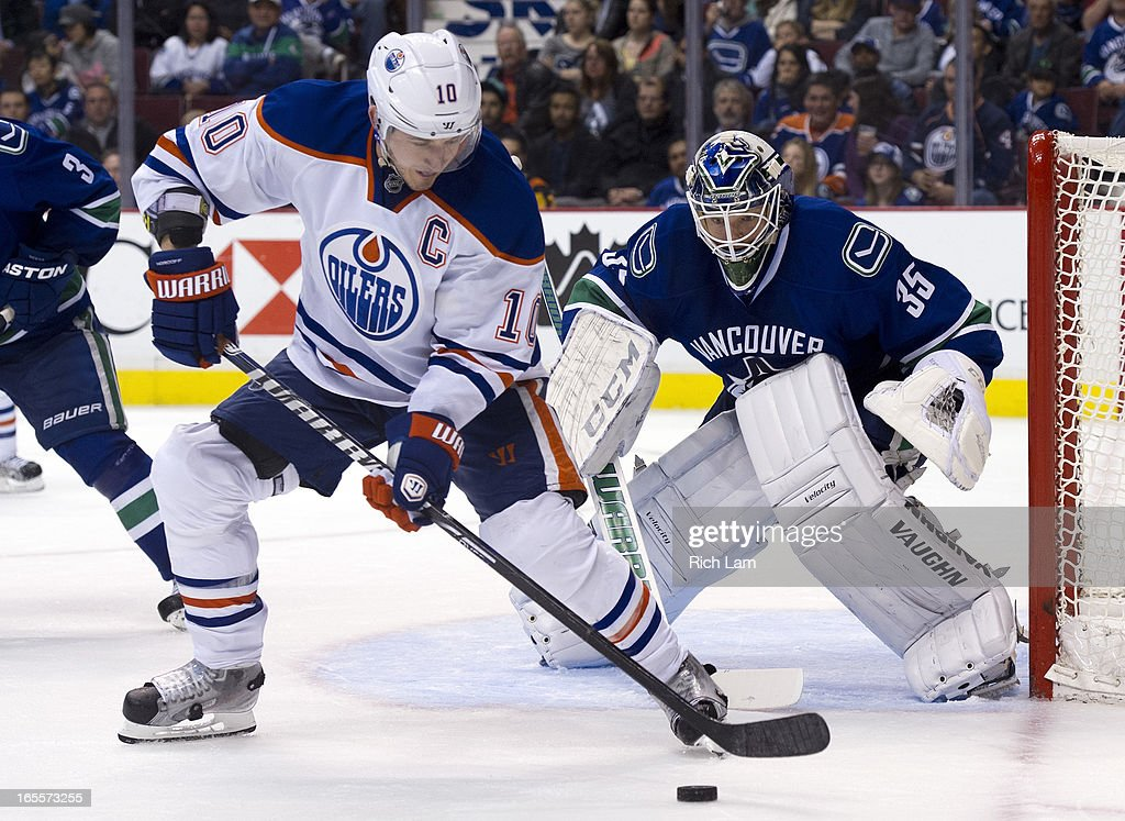 Goalie <a gi-track='captionPersonalityLinkClicked' href=/galleries/search?phrase=Cory+Schneider&family=editorial&specificpeople=696908 ng-click='$event.stopPropagation()'>Cory Schneider</a> #35 of the Vancouver Canucks keeps a close eye on <a gi-track='captionPersonalityLinkClicked' href=/galleries/search?phrase=Shawn+Horcoff&family=editorial&specificpeople=239536 ng-click='$event.stopPropagation()'>Shawn Horcoff</a> #10 of the Edmonton Oilers as he handles the puck at the side of the net during third period of NHL action on April 04, 2013 at Rogers Arena in Vancouver, British Columbia, Canada.