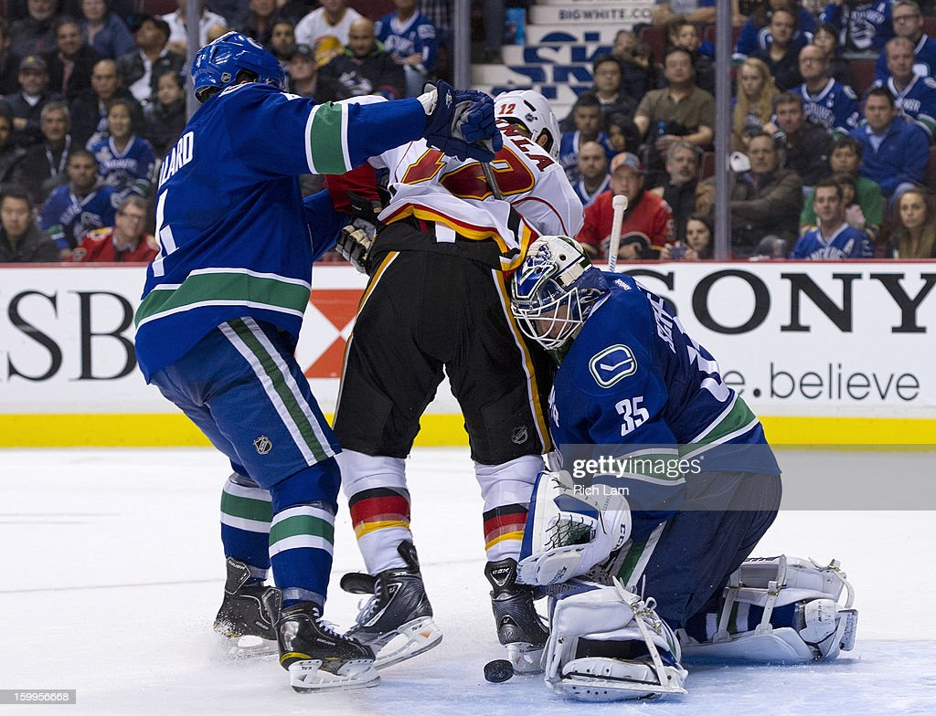 Goalie <a gi-track='captionPersonalityLinkClicked' href=/galleries/search?phrase=Cory+Schneider&family=editorial&specificpeople=696908 ng-click='$event.stopPropagation()'>Cory Schneider</a> #35 of the Vancouver Canucks makes a pad save while <a gi-track='captionPersonalityLinkClicked' href=/galleries/search?phrase=Keith+Ballard+-+Ice+Hockey+Player&family=editorial&specificpeople=630546 ng-click='$event.stopPropagation()'>Keith Ballard</a> #4 of the Vancouver Canucks and <a gi-track='captionPersonalityLinkClicked' href=/galleries/search?phrase=Jarome+Iginla&family=editorial&specificpeople=201792 ng-click='$event.stopPropagation()'>Jarome Iginla</a> #12 of the Calgary Flames battle in front of the net during the overtime period of NHL action on January 23, 2013 at Rogers Arena in Vancouver, British Columbia, Canada.