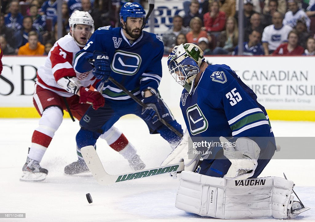 Goalie <a gi-track='captionPersonalityLinkClicked' href=/galleries/search?phrase=Cory+Schneider&family=editorial&specificpeople=696908 ng-click='$event.stopPropagation()'>Cory Schneider</a> #35 of the Vancouver Canucks makes a save while <a gi-track='captionPersonalityLinkClicked' href=/galleries/search?phrase=Justin+Abdelkader&family=editorial&specificpeople=2271858 ng-click='$event.stopPropagation()'>Justin Abdelkader</a> #8 of the Detroit Red Wings and <a gi-track='captionPersonalityLinkClicked' href=/galleries/search?phrase=Jason+Garrison&family=editorial&specificpeople=2143635 ng-click='$event.stopPropagation()'>Jason Garrison</a> #5 of the Vancouver Canucks look on during the third period in NHL action on April 20, 2013 at Rogers Arena in Vancouver, British Columbia, Canada.