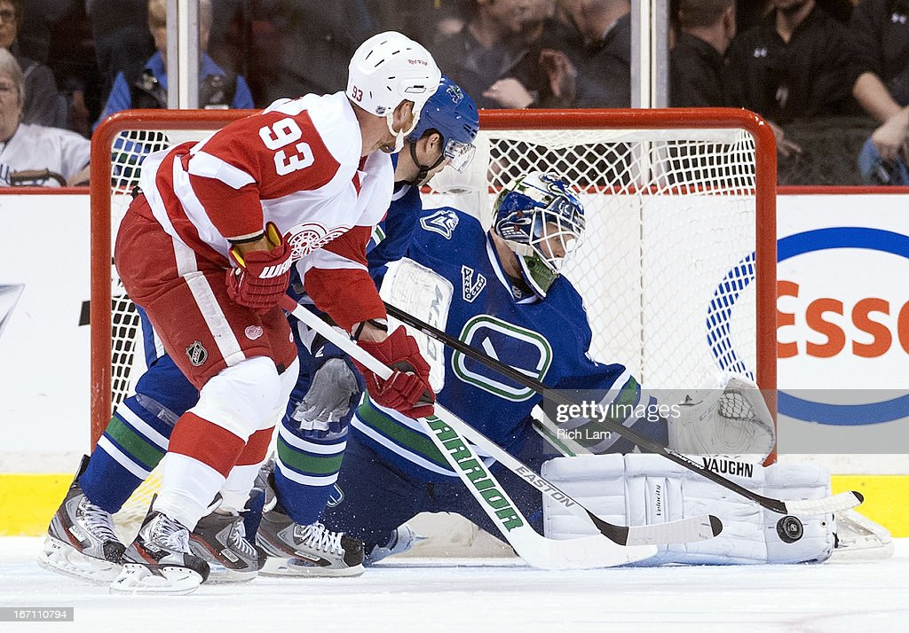 Goalie Cory Schneider #35 of the Vancouver Canucks stops Johan Franzen #93 of the Detroit Red Wings in close while Dan Hamhuis #2 of the Canucks tries to help defend on the play during the first period in NHL action on April 20, 2013 at Rogers Arena in Vancouver, British Columbia, Canada.