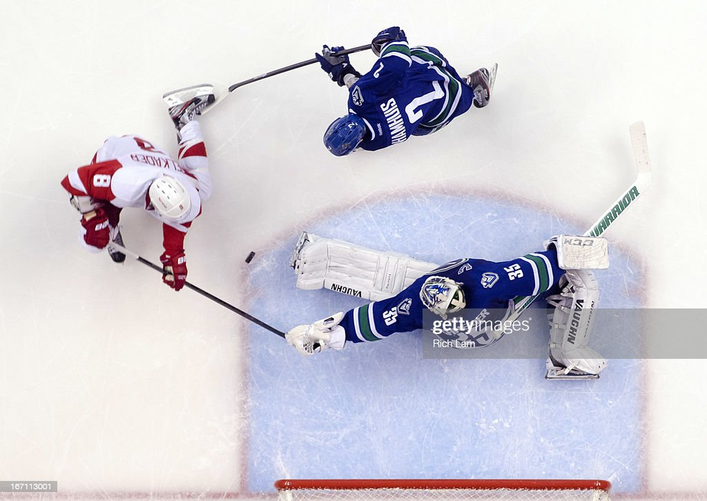 Goalie Cory Schneider #35 of the Vancouver Canucks stops Justin Abdelkader #8 of the Detroit Red Wings while Dan Hamhuis #2 of the Vancouver Canucks tries to help defend during the third period in NHL action to defeat the Red Wings 2-1 on April 20, 2013 at Rogers Arena in Vancouver, British Columbia, Canada.