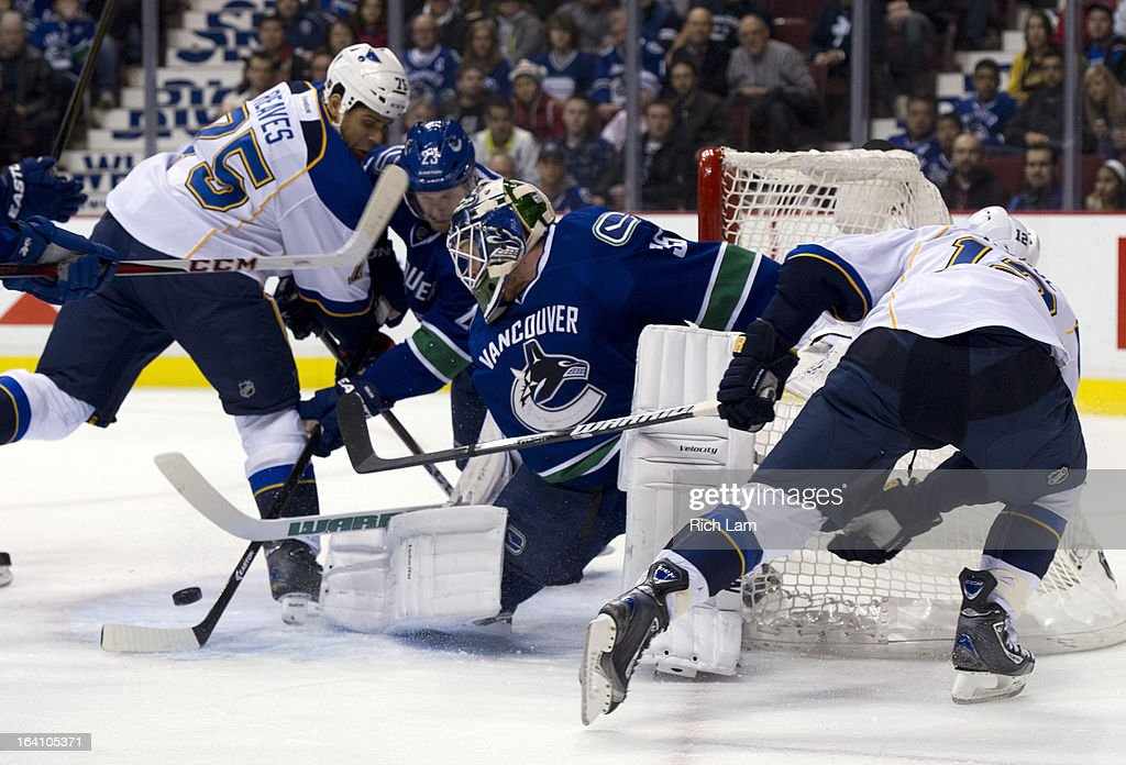 Goalie Cory Schneider of the Vancouver Canucks stops Scott Nichol of the St Louis Blues in close while Ryan Reaves of the St Louis Blues and...