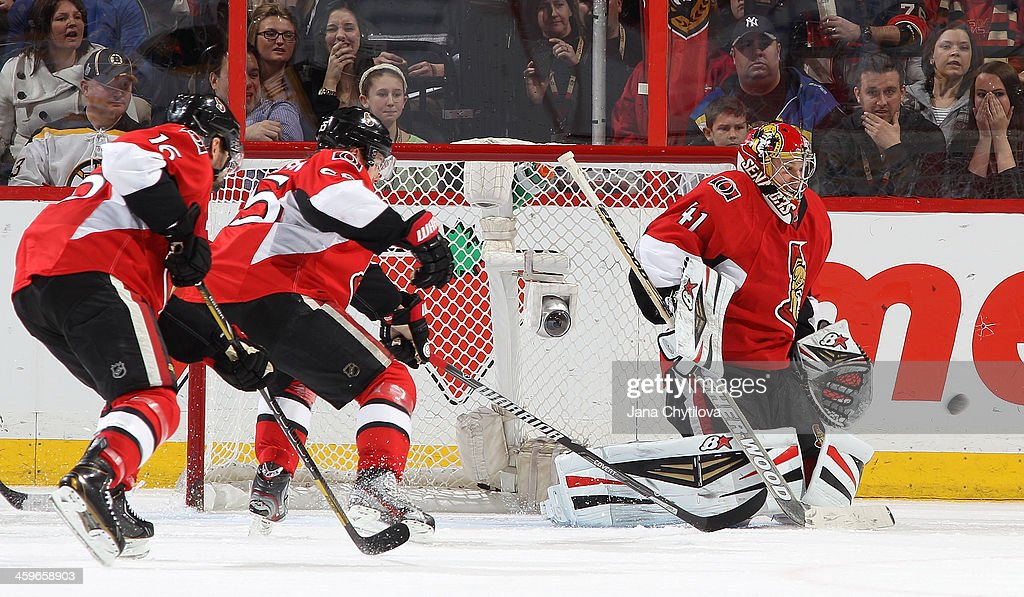 Goalie <a gi-track='captionPersonalityLinkClicked' href=/galleries/search?phrase=Craig+Anderson&family=editorial&specificpeople=211238 ng-click='$event.stopPropagation()'>Craig Anderson</a> #41 of the Ottawa Senators makes a late third-period save against the Boston Bruins as teammates <a gi-track='captionPersonalityLinkClicked' href=/galleries/search?phrase=Clarke+MacArthur&family=editorial&specificpeople=3949382 ng-click='$event.stopPropagation()'>Clarke MacArthur</a> #16 and <a gi-track='captionPersonalityLinkClicked' href=/galleries/search?phrase=Erik+Karlsson&family=editorial&specificpeople=5370939 ng-click='$event.stopPropagation()'>Erik Karlsson</a> #65 guard the net during an NHL game at Canadian Tire Centre on December 28, 2013 in Ottawa, Ontario, Canada.