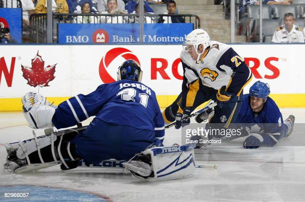 Goalie Curtis Joseph of the Toronto Maple Leafs blocks the net as teammate Carlo Colaiacovo trips up Drew Stafford of the Buffalo Sabres during a...