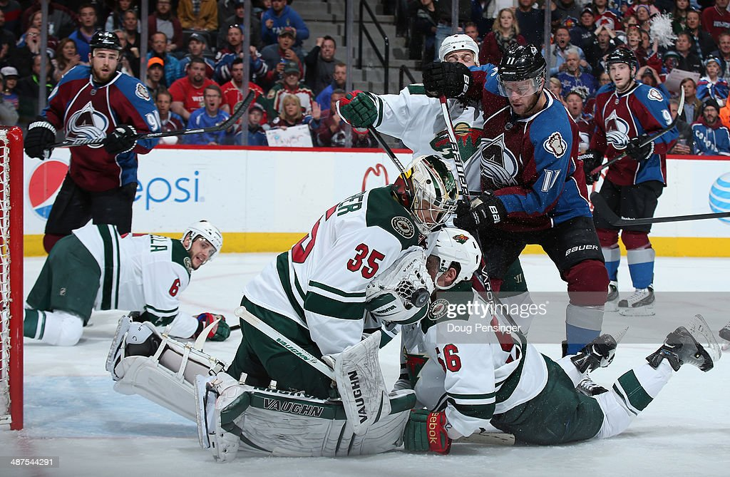 Goalie Darcy Kuemper of the Minnesota Wild knocks down the puck and covers it as he collides with teammate Erik Haula of the Minnesota Wild and Jamie...