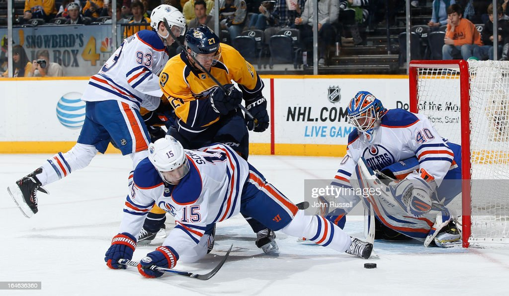 Goalie Devan Dubnyk #40 and Nick Schultz #15 of the Edmonton Oilers scramble to clear a loose puck against Patric Hornqvist #27 of the Nashville Predators during an NHL game at the Bridgestone Arena on March 25, 2013 in Nashville, Tennessee.