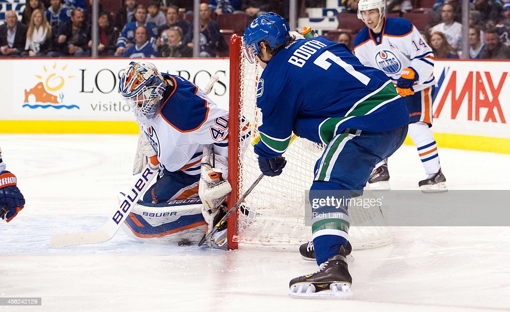 Goalie Devan Dubnyk of the Edmonton Oilers stops David Booth of the Vancouver Canucks on a wrap around attempt during the second period in NHL action...