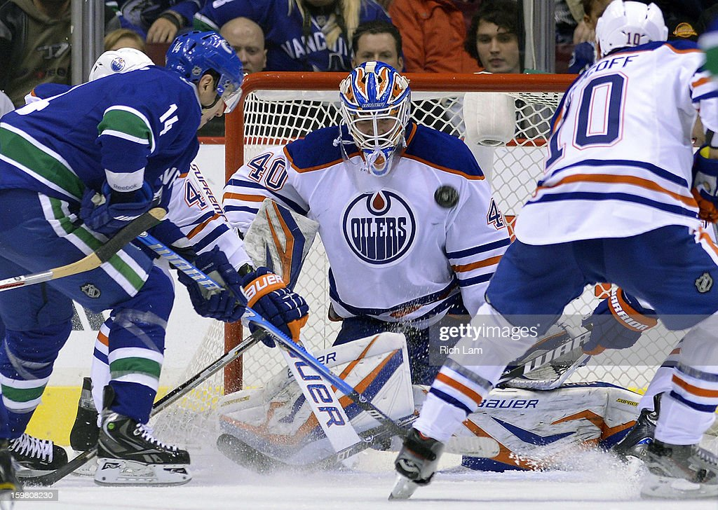 Goalie Devan Dubnyk #40 of the Edmonton Oilers watches an airborne puck fly across the front of the net as Alexandre Burrows #14 of the Vancouver Canucks and Shawn Horcoff #10 of the Edmonton Oilers look on during the third period of NHL action on January 20, 2013 at Rogers Arena in Vancouver, British Columbia, Canada.