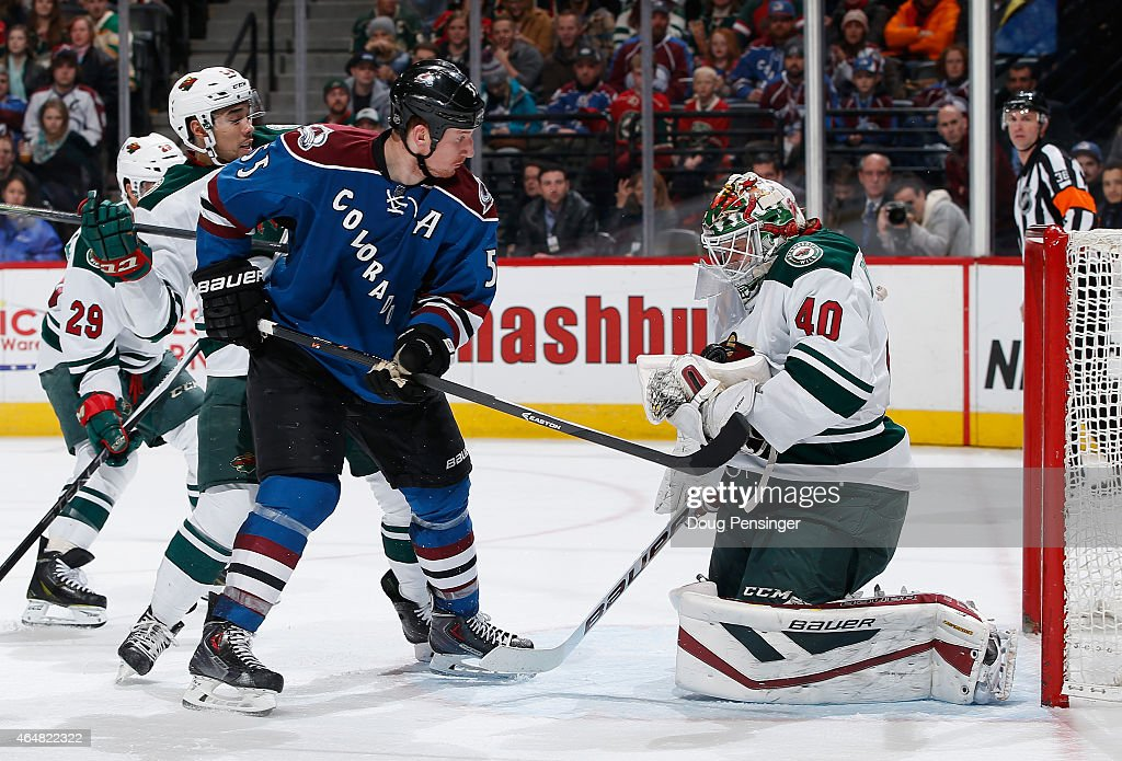 Goalie Devan Dubnyk of the Minnesota Wild makes a save and collects the puck as Cody McLeod of the Colorado Avalanche looks for a rebound against...