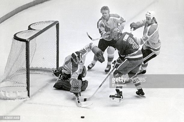 Goalie Don McLeod of the Vancouver Blazers poke checks the puck away from Richard Farda of the Toronto Toros as McLeod's teammates Johnny McKenzie...